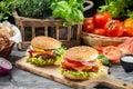 Dos hamburguesas hechas en casa hicieron ââfrom verduras frescas en la tabla de madera vieja Imágenes de archivo libres de regalías