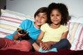 Dos niños que se sientan en sofa watching tv junto Foto de archivo