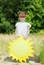 Dosyć miedzianowłosa dziewczyna pozuje z papierowym słońcem Fotografia Stock