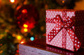 Dotted christmas gift box on blurred lights background a shot of and tree in the selective focus Royalty Free Stock Images