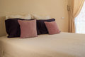 Double bed with purple cushions Royalty Free Stock Images