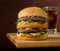 Double cheeseburger and soda a classic style with two beef patties sauce lettuce cheese pickles onions on a sesame seed bun with Royalty Free Stock Images