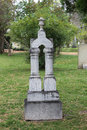 Double column marble headstone in old cemetery with grass and trees backgound Royalty Free Stock Photography