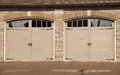 Double garage doors driveway with windows and pebbled stone Stock Image
