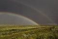 Double rainbow over the green meadow. Royalty Free Stock Photo