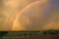 Double rainbow vibrant with green farmland and stormy sky at sunset Royalty Free Stock Photo