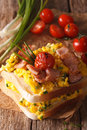 Double sandwich with scrambled eggs, bacon and tomatoes close-up Royalty Free Stock Photo