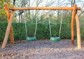 Double swing at public school playground in autumn Stock Photo