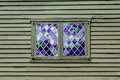 Double window with purple panes in a diamond pattern in the wall of a colonial building Royalty Free Stock Photo