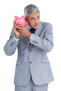 Doubtful businessman holding piggy bank on white background Stock Photo