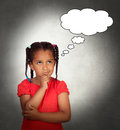 Doubtful little girl with a blank bubble on over gray background Royalty Free Stock Images