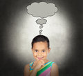 Doubtful little girl with a bubble on over gray background Royalty Free Stock Images