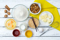 Dough recipe ingredients baking cake in rural kitchen eggs flour milk butter sugar with yellow napkin on white wooden table from Stock Photo