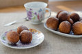 Doughnut balls freshly baked cheese donuts with powdered sugar on a plate with parchment paper and a mug Stock Photos