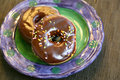 Doughnut with chocolate frosting and sprinkles icing multi colored Royalty Free Stock Image