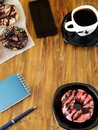 Doughnut with pink glazing, cup of coffee and stationery on a wooden table.