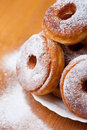 Doughnuts with sugar stack of sweet and caloric holes and powdered lying on white plate white strewed on food and table Stock Photo