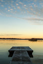 Down by the jetty calm scandinavian lake in sunset with Royalty Free Stock Photos