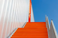 Down the orange emergency staircase against blue sky Royalty Free Stock Image