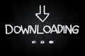 Downloading writting with down sign arrow drawn with chalk on blackboard Royalty Free Stock Image
