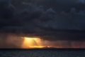 Downpour and sun rays on the sea at sunset Royalty Free Stock Images