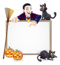 Dracula halloween sign a with a classic vampire character pointing down and witch s black cats broomstick and carved Stock Photography