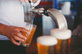 Draft beer pour in a glass from the crane Royalty Free Stock Image