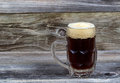 Draft stout beer in glass stein on rustic wood horizontal image of a filled with dark Royalty Free Stock Photography