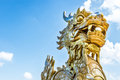 Dragon statue in vietnam as symbol and myth golden stone with face close up on blue sky background leftside view of vietnamese Stock Image