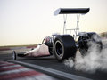 Dragster racing down the track with burnout