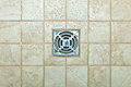 Drain hole metal in the tiled floor of a shower Stock Photos
