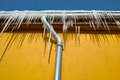 Drain pipe on the building yellow wall of house in winter season with icicles and for water Stock Image