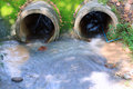 Drain pipes water flowing out of two concrete Stock Images