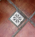 Drain water flows through a metal hole cover buried in the pavement Royalty Free Stock Image