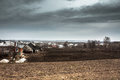 Dramatic agricultural countryside landscape with moody sky and cultivated field of farmer`s plantation