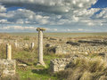 Dramatic blue sky with white clouds over the ruins of an ancient greek column at Histria, on the shores of Black Sea. Histria is t