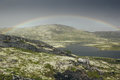 Dramatic landscape with beautiful rainbow over arctic meadows, mountain and lake. Royalty Free Stock Photo