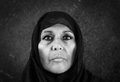 Dramatic muslim woman in bw blackand white portrait of serious middle aged with black scarf or hijab Royalty Free Stock Photo