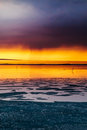 Dramatic orange and violet sunset over a wintry lake in winter Royalty Free Stock Images
