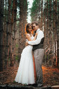 Dramatic picture bride and groom on the background of leaves forest backlight Royalty Free Stock Photo