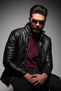 Dramatic shot of a young man with beard in leather jacket and sunglasses Stock Photos