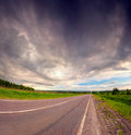 Dramatic sky under country asphalt road. Royalty Free Stock Photo