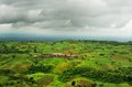 Dramatic sky and wide angle landscape this picture is taken from above a hill looking over a small village in central india Royalty Free Stock Photo
