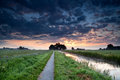 Dramatic summer sunrise over farmland with canal and fields Stock Photos