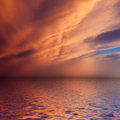Dramatic sunset with clouds reflected in water Stock Images