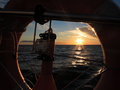 Dramatic sunset over the baltic sea beatiful with clouds view from sailboat through rescue wheel vacation travel Stock Photography