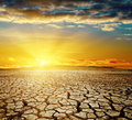 Dramatic sunset over cracked earth Royalty Free Stock Photo