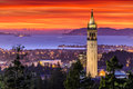 Dramatic sunset over san francisco bay and the campanile beautiful uc berkeley with golden gate bridge in background Royalty Free Stock Images