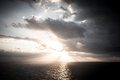 Dramatic sunset rays through a cloudy dark sky over the ocean Royalty Free Stock Photo