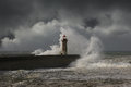 Dramatic wave over light house heavy storm weather conditions Stock Photo